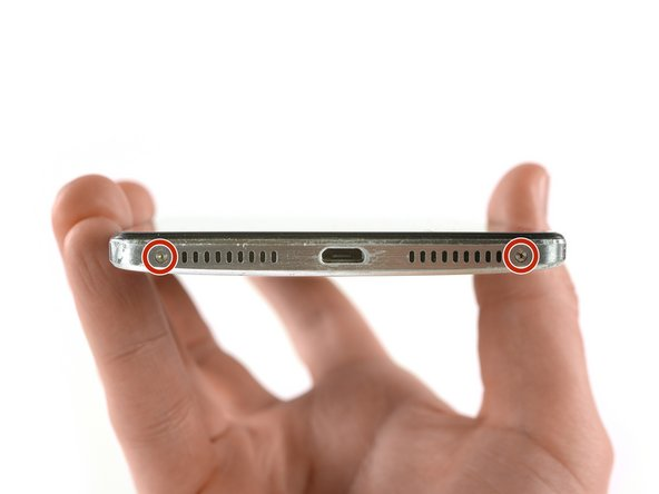 دو عدد پیچ Torx T2 که در انتهای دستگاه موبایل قرار دارند را، باز کنید. این پیچها در تصویر با رنگ قرمز علامت گذاری شدهاند.