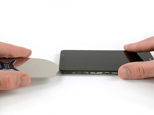 پس از آنکه چسب زیر قسمت بالایی صفحه نمایش اندکی نرم شد، یک قاب بازکن را با احتیاط میان صفحه نمایش و فریم میانی قرار دهید.