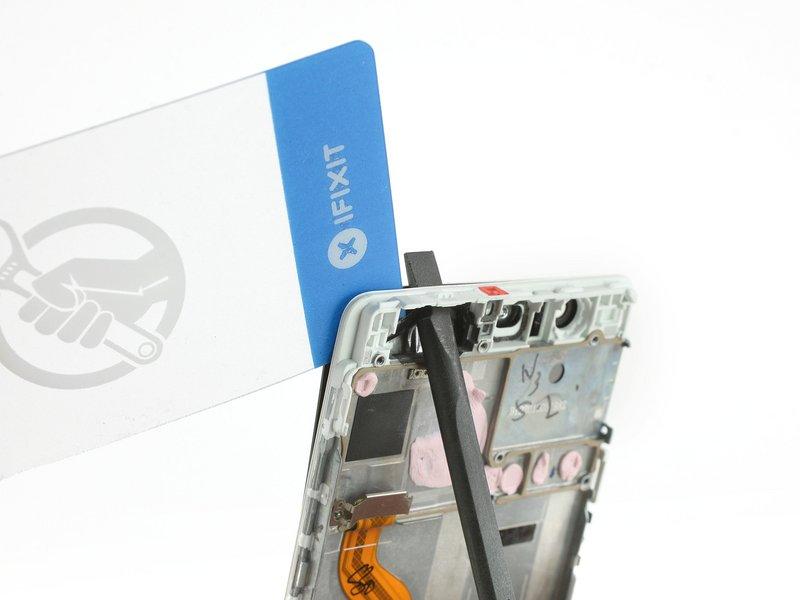یک کارت پلاستیکی و یا دو عدد قاب بازکن را زیر قسمت بالایی صفحه نمایش، میان صفحه نمایش با فریم قرار دهید.