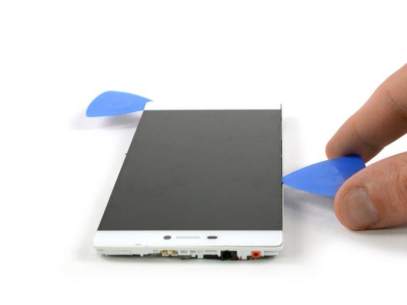 یک قاب بازکن را در فاصله ایجاد شده مابین صفحه نمایش و فریم میانی قرار دهید. دقت کنید که فقط سر قاب بازکن باید درون این فاصله قرار گیرد. سپس قاب بازکن را در راستای سمت چپ حرکت دهید تا صفحه نمایش را از فریم جدا کنید.