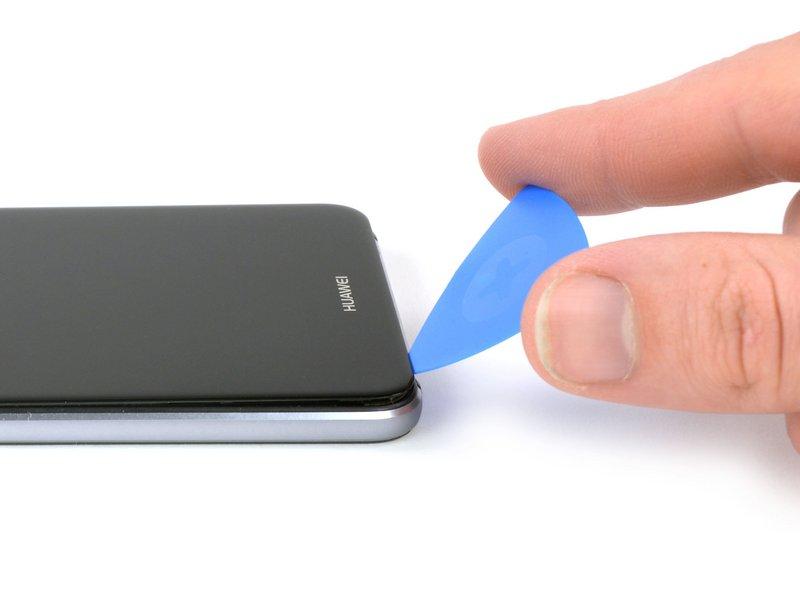 نوک یک قاب بازکن را میان شکاف صفحه نمایش و فریم میانی قرار دهید.