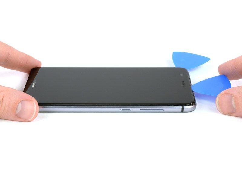 پس از آن که قاب بازکن را دور تا دور گوشی حرکت دادید، قاب بازکن را در بالای گوشی به اندازه کمی چرخانده تا صفحه نمایش از فریم میانی جدا شود.