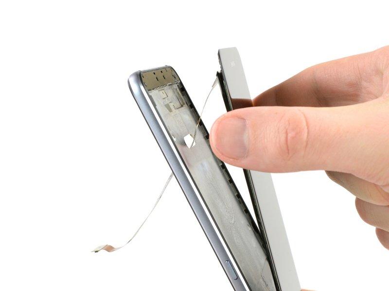 قسمت بالایی گوشی را در دست گرفته و با عبور دادن کابل منعطف از شکافی که در تصویر میبینید، صفحه نمایش را از فریم جدا کنید.