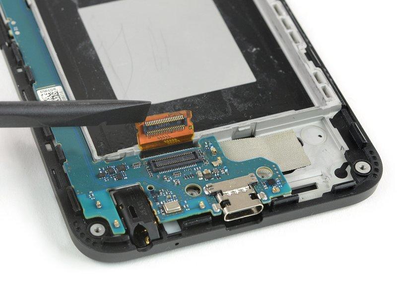 با استفاده از ته صاف اسپاتول، اتصال کابل فلت صفحه نمایش را جدا کنید.