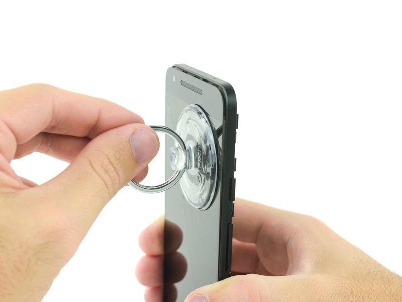 یک ساکشنکاپ را نزدیک لبه بالای صفحه نمایش بچسبانید و توسط آن، صفحه نمایش را از فریم میانی کمی دور کنید. اگر جدا کردن صفحه نمایش از فریم دشوار است، آن را مجددا حرارت دهید.