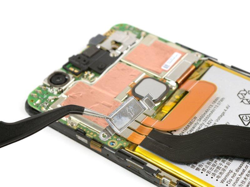 پیچ محافظ کابلهای باتری مشخص شده در تصویر را باز کنید؛ سپس محافظ را با پنس جدا کنید.