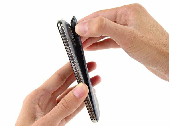 با ناخن انگشت یا قاببازکن پلاستیکی کاور گوشی را باز کنید