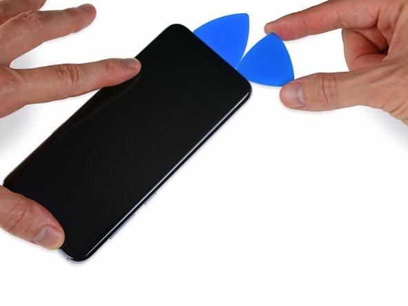 با یک قاببازکن چسب زیر لبهی چپ نمایشگر را جداکنید.