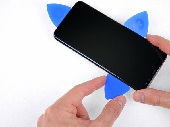 با قاببازکن چسب زیر لبهی راست نمایشگر را جدا کنید