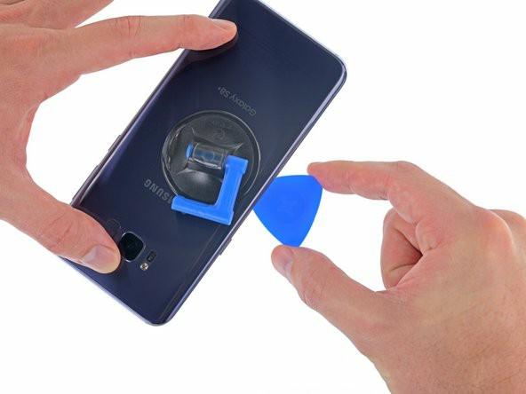 قاببازکن را در طول لبهی چپ گوشی تا پایین بلغزانید تا چسب نگهدارندهی کاور پشت باز شود