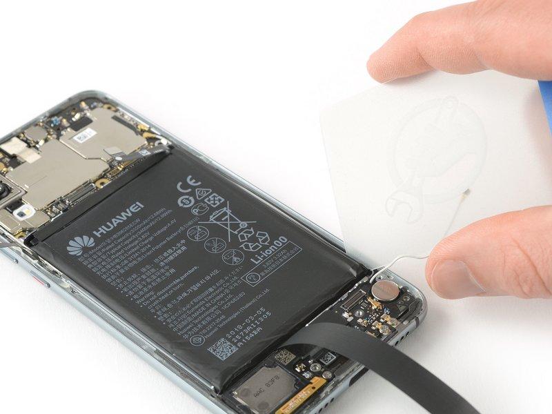 یک کارت پلاستیکی را زیر قسمت انتهایی گوشه سمت راست باتری قرار دهید تا چسب برش بخورد.