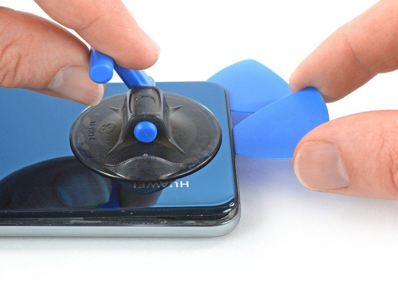 قاب بازکن دوم را درون فاصله ایجاد شده قرار دهید و آن را به گوشه سمت چپ پایین دستگاه موبایل ببرید تا چسب برش بخورد.