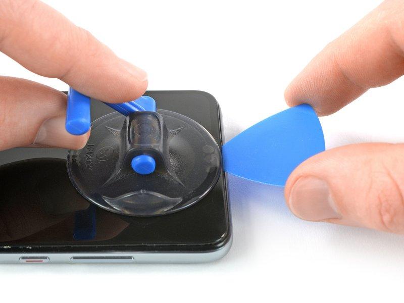 ساکشن کاپ را به سمت بالا کشیده و پس از ایجاد شکافی جزئی، یک قاب بازکن میان صفحه نمایش شیشهای و قاب پلاستیکی قرار دهید. با حرکت دادن قاب بازکن به سمت گوشه چپ بالایی دستگاه موبایل، چسب را برش بزنید.