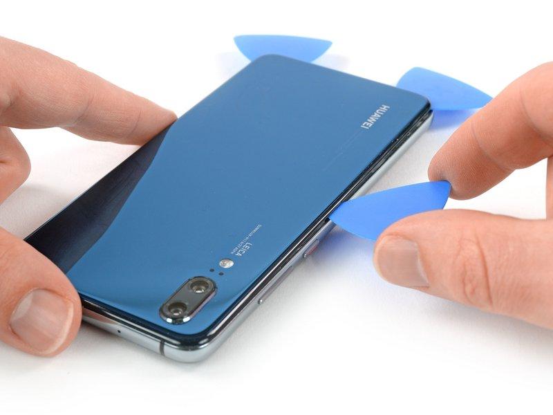 قاب بازکن را از گوشه سمت چپ در انتهای دستگاه موبایل در راستای طولی به سمت بالا ببرید تا چسب زیرین برش بخورد.
