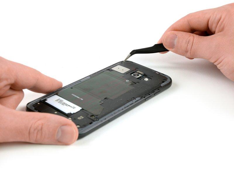 با استفاده از پنس مطابق تصویر، گیرههای نگهدارنده محافظ برد را آزاد کنید و محافظ مادربرد، که شامل تراشه NFC و اسپیکر میباشد را جدا کنید