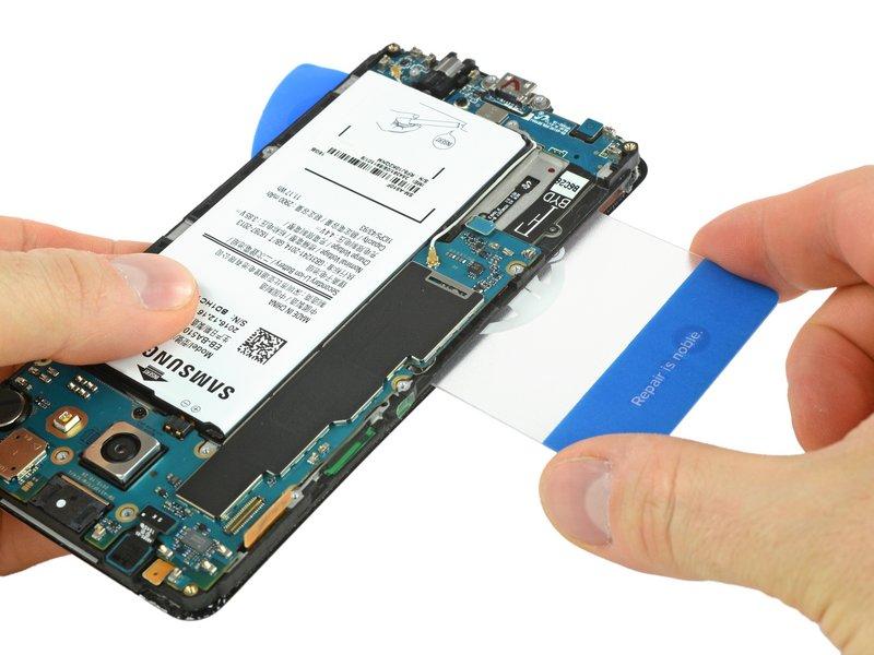 قاببازکن را مانند تصویر، به سمت چپ دستگاه در جایی که برد اصلی قرار دارد فرو کنید تا به چسبهای باتری برسد