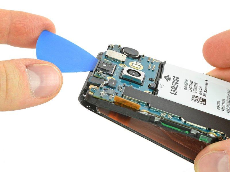 صفحه نمایش را مانند تصویر، از فریم دستگاه جدا کنید و باقیمانده چسب در بالای دستگاه را با قاببازکن جدا کنید