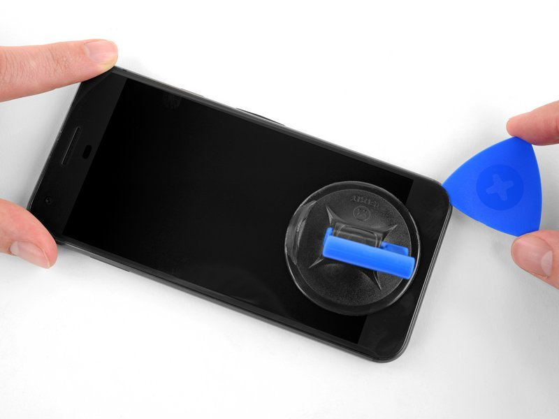 یک قاببازکن را درون شکاف ایجاد شده، بین صفحه نمایش و فریم میانی فرو کنید. قاببازکن را در امتداد لبه دستگاه بکشید تا چسبهای این قسمت جدا شوند. هشدار: صفحه نمایش به شدت شکننده است. اگر قصد استفاده مجدد از آن را دارید، مراقب باشید قاببازکن را فقط در حدی که در مرحله ۲ ذکر شده فرو کنید، تا صفحه نمایش آسیب نبیند.