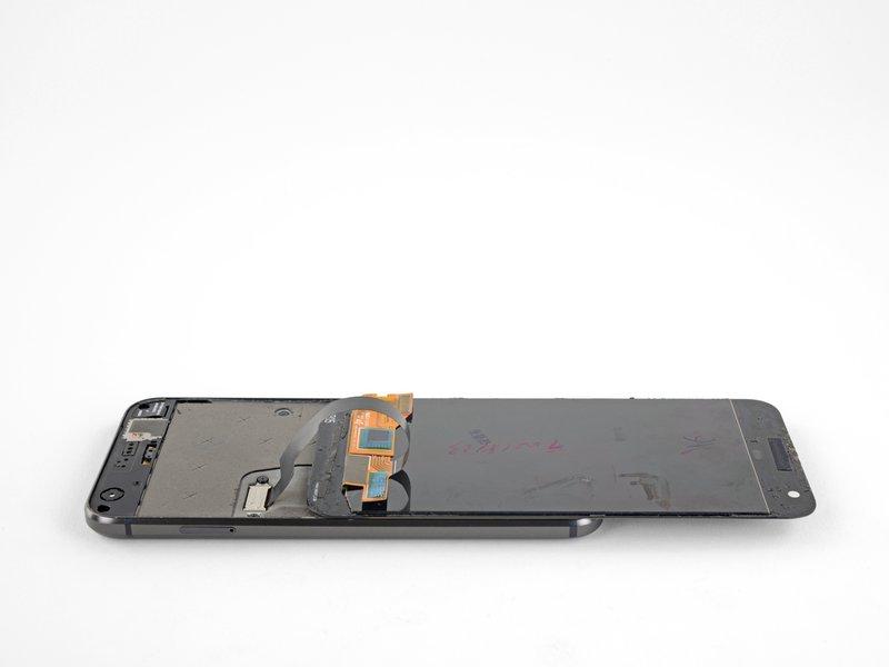 بعد از جدا کردن چسبها، صفحه نمایش را از قسمت بالای گوشی بلند کنید و مانند تصویر، به سمت پایین گوشی بچرخانید.