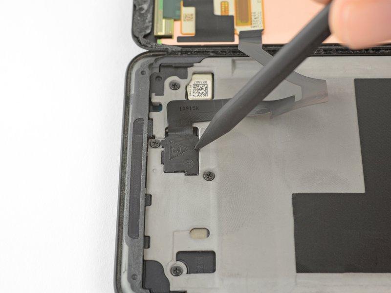 نوک اسپاتول را داخل سوراخ زیر محافظ اتصال صفحه نمایش فرو کنید.