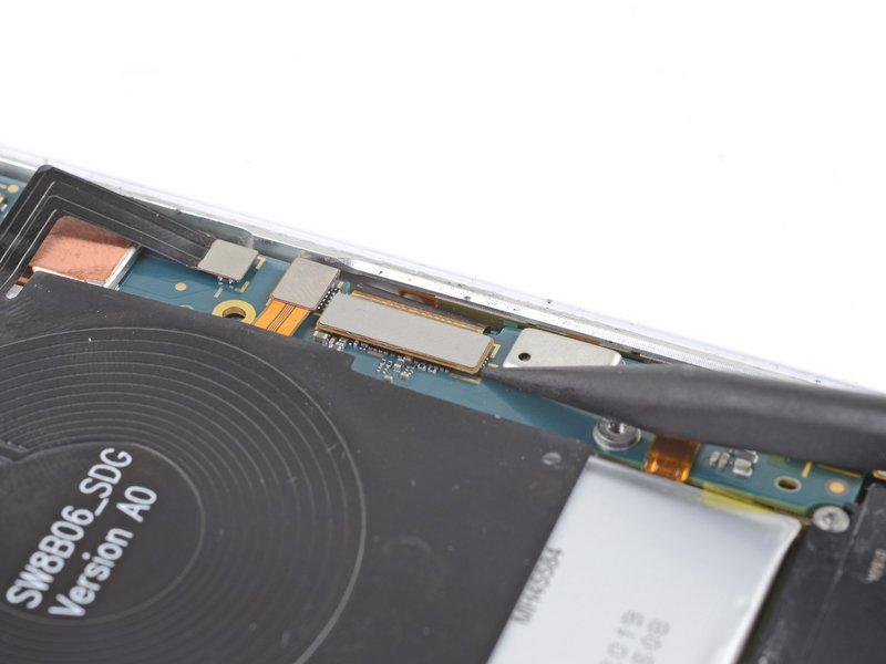 با استفاده از نوک اسپاتول کابل صفحه نمایش را از مادربرد جدا کنید.