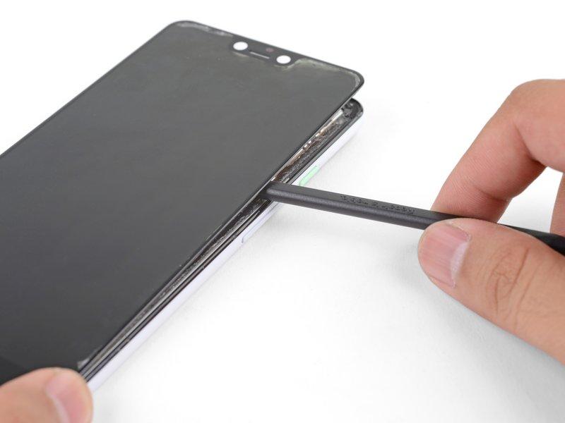صفحه نمایش هنوز توسط چسبی که در مرکز آن قرار دارد متصل است. یک قاببازکن پلاستیکی را از لبه سمت چپ دستگاه به زیر صفحه نمایش فرو کرده و چسبها را جدا کنید.