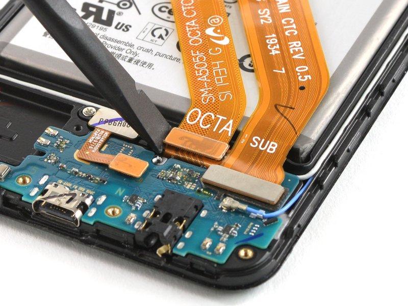 با استفاده از ته صاف اسپاتول، کابل فلت صفحه نمایش و کابل مجاورش را جدا کنید
