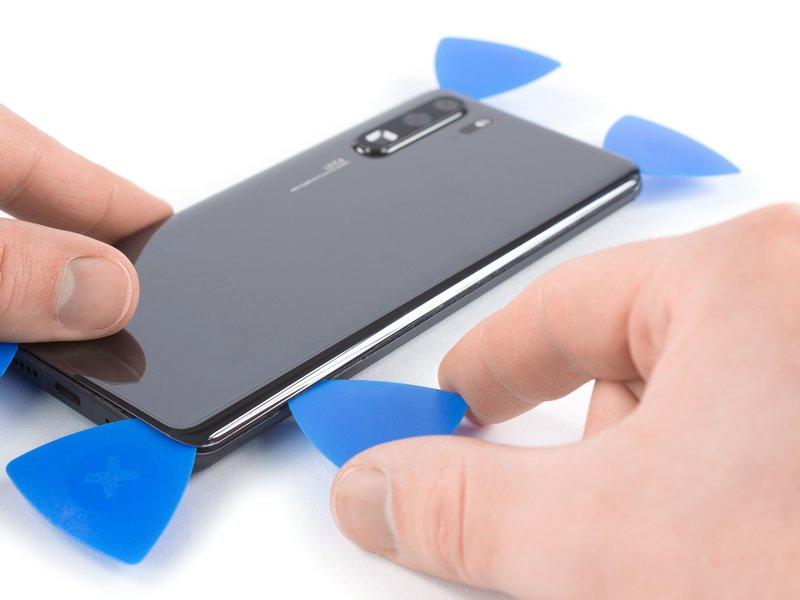 این قاب بازکن را در راستای طولی دستگاه موبایل به سمت پایین بکشید تا چسب برش بخورد.