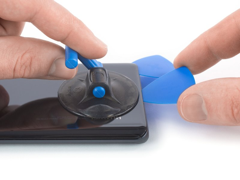 قاب بازکن دوم را درون شکاف قرار داده و آن را به سمت گوشه چپ پایین دستگاه موبایل بکشید تا چسبها برش بخورند.
