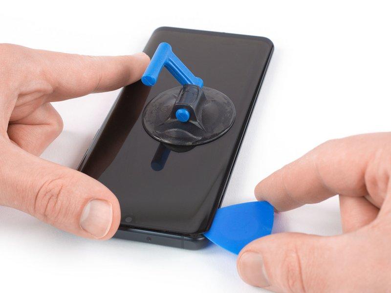 قاب بازکن را به گوشی سمت چپ بالای گوشی برده تا چسب برش بخورد.