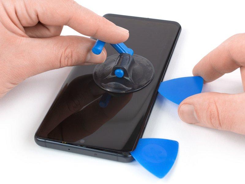 قاب بازکن دوم را درون شکاف قرار داده و آن را به سمت گوشه چپ در پایین دستگاه موبایل کشیده تا چسب برش بخورد.