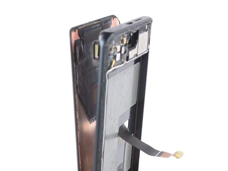 کابل منعطف صفحه نمایش را از میان سوراخی که در فریم میانی قرار دارد، رد کرده و صفحه نمایش را از دستگاه موبایل جدا کنید.