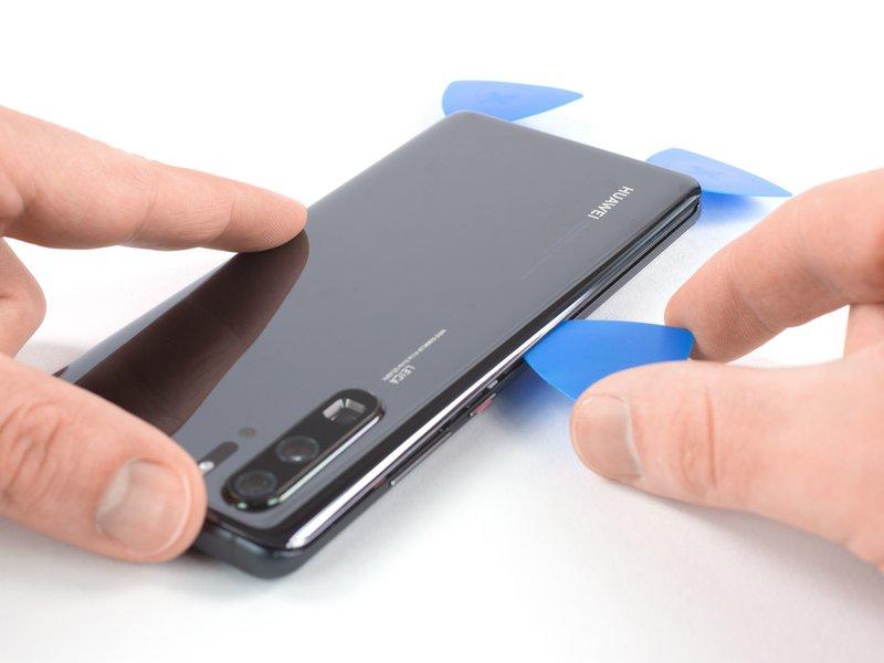 قاب بازکن را از گوشه چپ پایین دستگاه موبایل در راستای طولی حرکت دهید تا چسب برش بخورد.