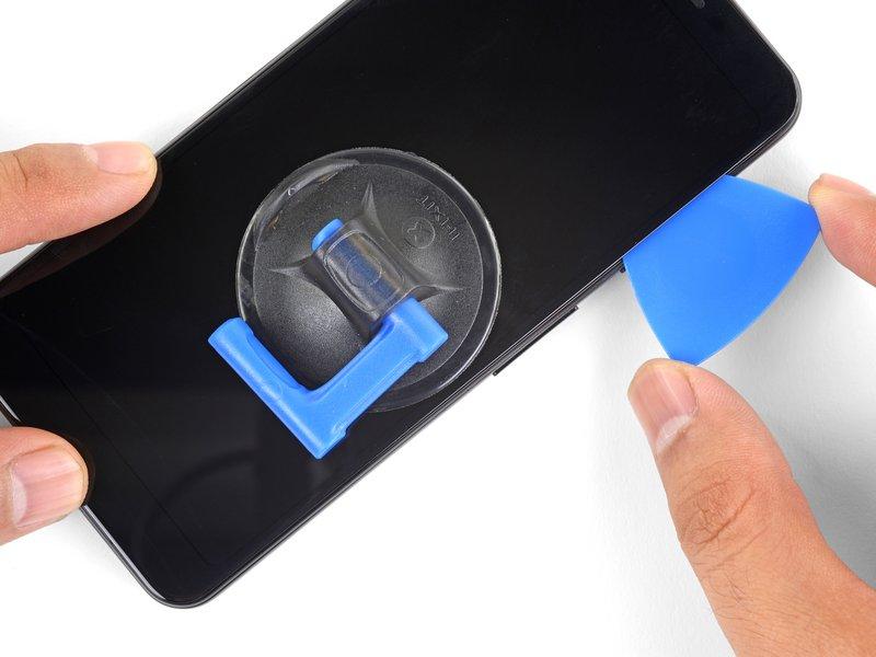قاببازکن را در امتداد لبه سمت راست دستگاه بکشید تا چسبهای این قسمت جدا شوند. هشدار: قاببازکن را بیشتر از 6 میلیمتر فرو نکنید؛ در غیر این صورت ممکن است به کابل فلت صفحه نمایش آسیب برسانید. برای جلوگیری از بسته شدن مجدد چسبها، قاببازکن را در لبه سمت راست دستگاه رها کنید.