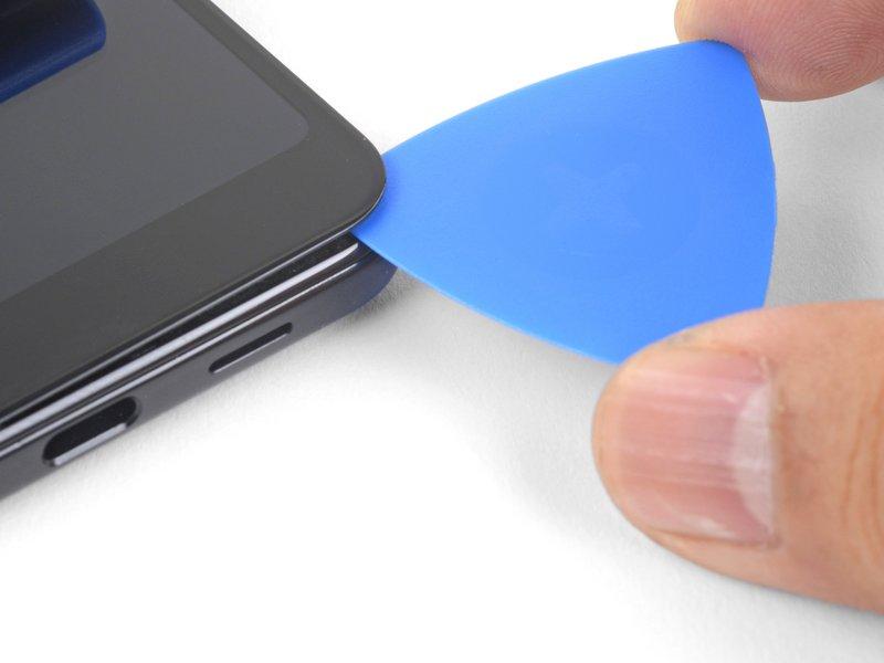 یک قاببازکن را در شکاف گوشه پایین سمت راست صفحه نمایش وارد کنید. سپس آن را در امتداد لبه پایین صفحه نمایش بکشید تا چسبهای این لبه نیز جدا شوند.