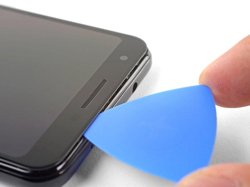 چسبهای لبه بالای صفحه نمایش را جدا کنید؛ توجه داشته باشید قاببازکن را بیشتر از 8 میلیمتر فرو نکنید.