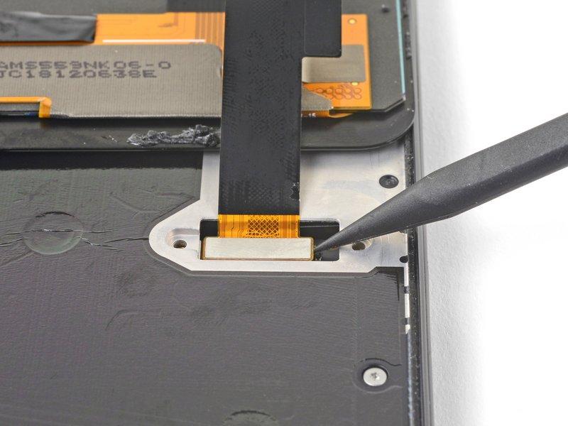 با استفاده از نوک اسپاتول اتصال کابل صفحه نمایش را جدا کنید.