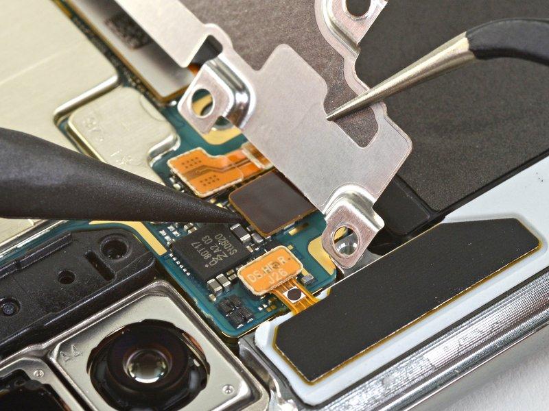 با استفاده از نوک اسپاتول، اتصال سیم برد شارژ بیسیم را از مادربرد جدا کنید.