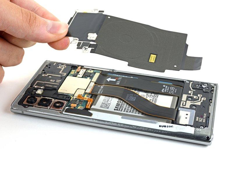 محافظ فلزی برد شارژ بیسیم را به سمت بالا متمایل کنید. سپس برد شارژ را از دستگاه جدا کنید.